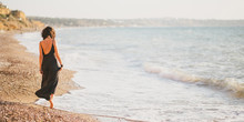 Young Woman In Black Dress Walking Barefoot On Beach Near Ocean. Summer Weekend