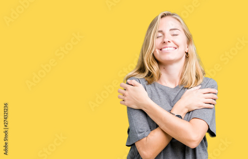 Obraz Beautiful young woman wearing oversize casual t-shirt over isolated background Hugging oneself happy and positive, smiling confident. Self love and self care - fototapety do salonu
