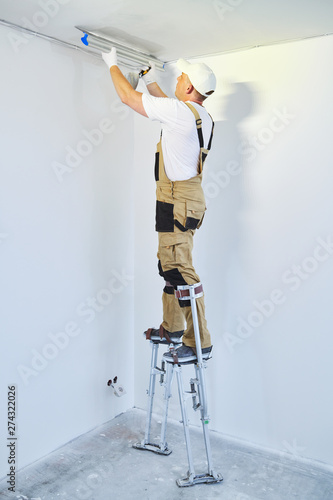 Painter in stilts with putty knife Tablou Canvas