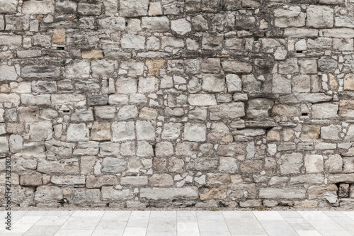 Fotomural Gray rough stone wall and white floor tiling