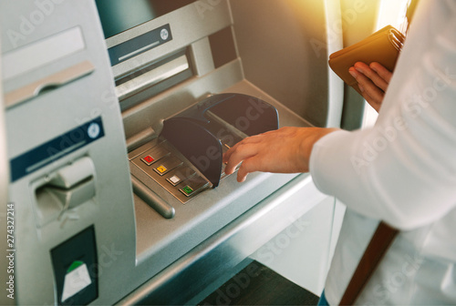 Woman using ATM holding wallet an pressing the PIN security number on the keyboa Canvas Print