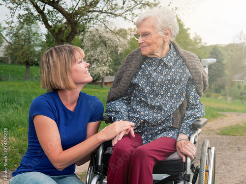 Young woman and senior with wheelchair in the park