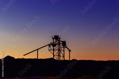 Photo construction aggregate near the heaps of gravel at sunset