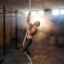 Strong Young Crossfitter Climbing On The Rope During Training.