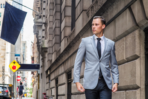 Photo Young European Businessman traveling in New York City, wearing gray blazer, white shirt, black tie, black pants, walking on vintage street with high buildings, flag, cars, looking away