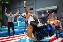Happy Young Friends Playing Mechanical Bull Game