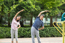 Happy Mature Couple Exercising In Park
