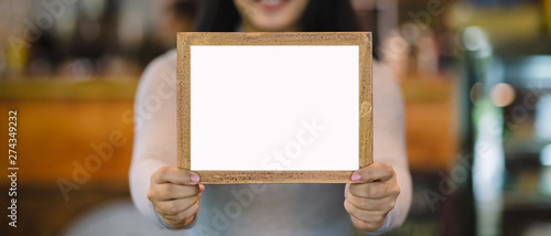 woman holding blank wooden frame in coffee shop Canvas Print