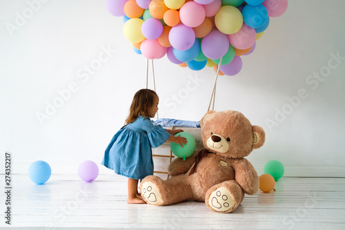 A little girl is celebrating her birthday. Big Teddy bear in a birthday present.