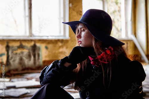 Foto auf Acrylglas Girl in a black cloak and hat sitting in a ruined room. Photo shoot in an unusual place