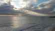 Calm Ocean with a Sunset Over the Horizont and a Cloudy Sky
