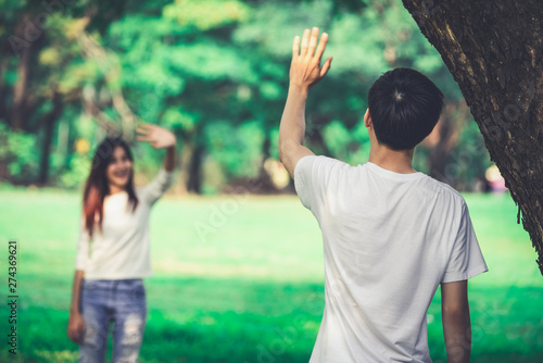 фотография Young people, man and woman greeting or saying goodbye by waving hands in the park