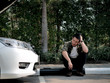 Stressed Asian man with car problem and sitting on pathway and cry, lifestyle concept.