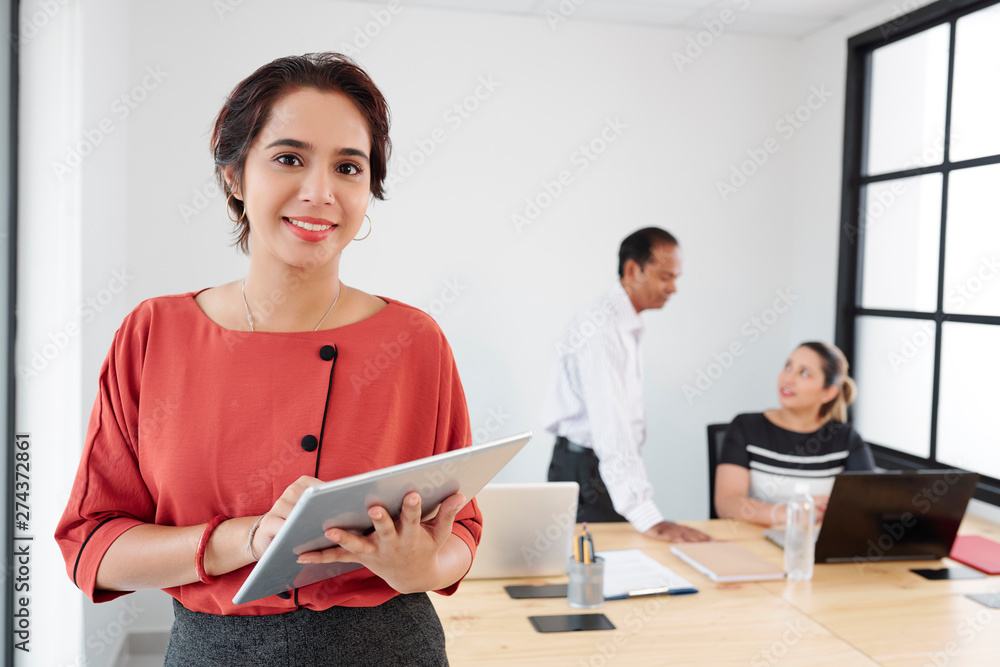 Fototapeta Portrait of Indian young businesswoman using tablet pc and smiling at camera with her colleagues working together in the background