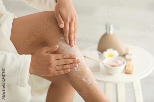Fototapeta Beautiful young woman applying body scrub at home