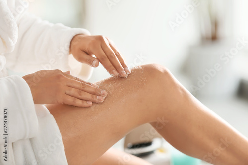Fototapeta Beautiful young woman applying body scrub at home, closeup