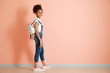 Stylish African-American girl in jeans overall near color wall