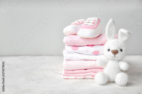 Stack of clothes, shoes and toy on table Wallpaper Mural