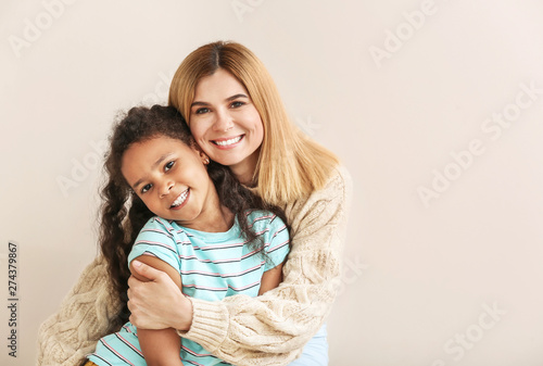 Photo Happy woman with little adopted African-American girl on white background