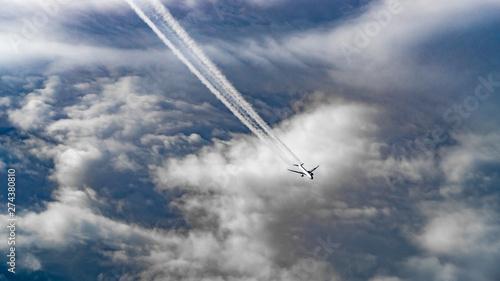 Luftaufnahme auf ein unter uns fliegendes Flugzeug mit Kondensstreifen Wallpaper Mural