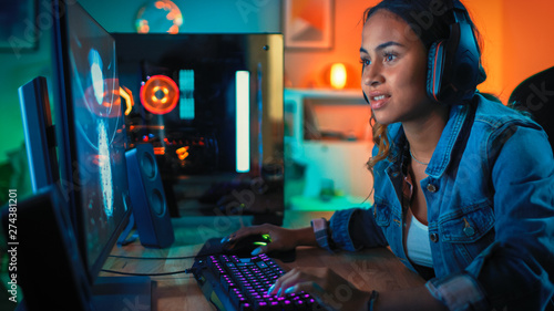 Pretty and Excited Black Blogger Girl in Headphones is Playing First-Person Shooter Online Video Game on Her Computer Wallpaper Mural