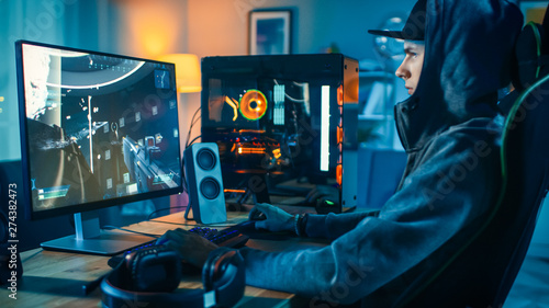 Photo Professional Gamer and Streamer Playing First-Person Shooter Online Video Game on His Cool Personal Computer