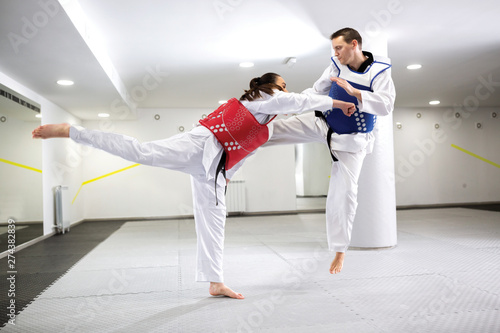 A Guy and a girl in close taekwondo combat training - Buy