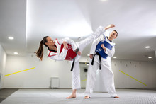 Young Woman Training Martial Art Of Taekwondo With Her Coach