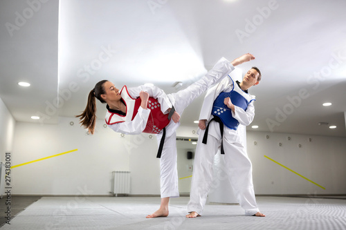 Fototapeta Young woman training martial art of taekwondo with her coach
