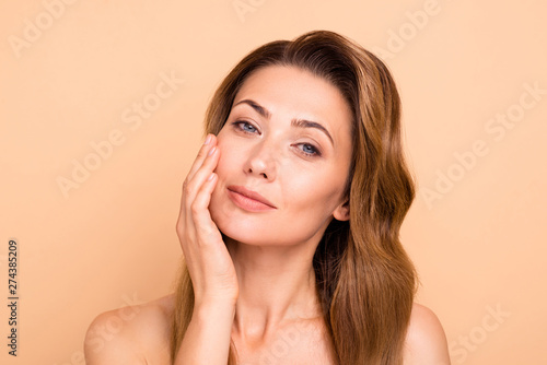 Fototapeta Close up photo beautiful amazing mature she her lady overjoyed after salon spa procedures aesthetic pretty ideal appearance nude arm hand palm touch cheek perfection isolated pastel beige background obraz