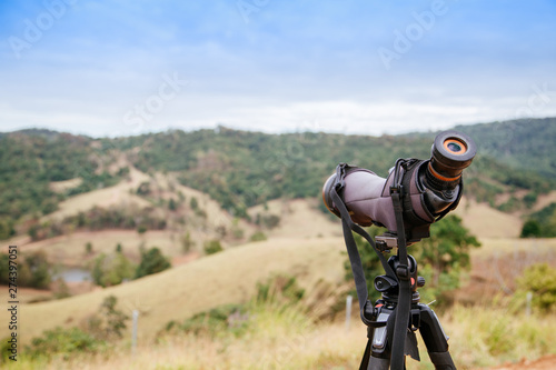 Fotografía  spotting scope or monocular on blurred green mountain as background