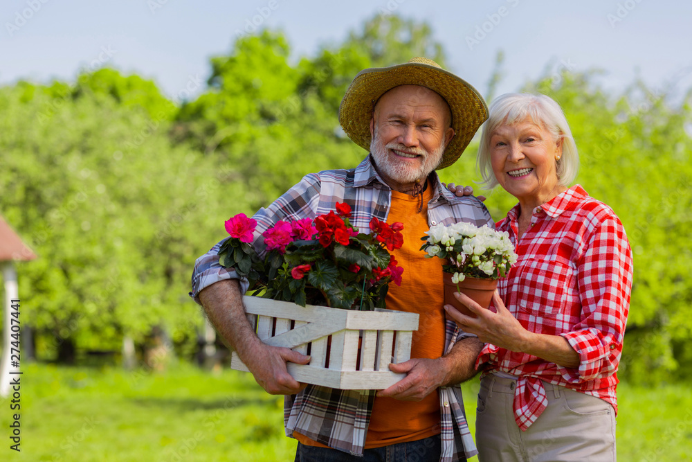 Fototapety, obrazy: Husband and wife smiling broadly standing with flower pots