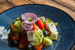 Greek salad in a plate on a wooden table.
