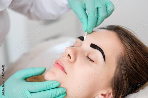 Beautician performing henna brows correction Billede på lærred