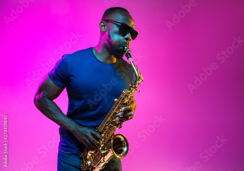 canvas print motiv - master1305 : Young african-american jazz musician playing the saxophone on pink studio background in trendy neon light. Concept of music, hobby. Joyful attractive guy improvising. Colorful portrait of artist.
