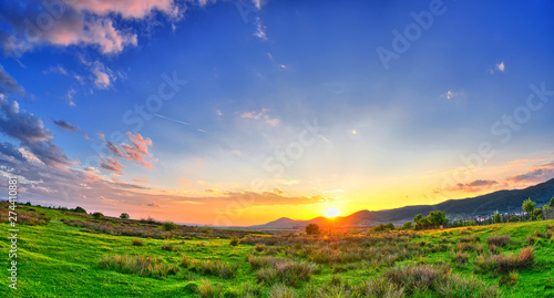 Obraz Colorful Summer sunset with sun rays coloring the clouds - fototapety do salonu