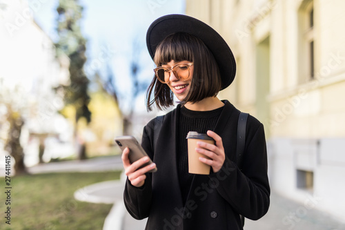 Fotografia Young woman in black hat standing at the street drinking coffee to go and using
