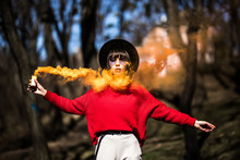 Girl Holding A Orange Smoke Bomb In The Park
