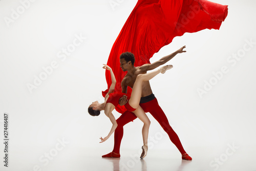 Fototapeta Graceful classic ballet dancers dancing isolated on white studio background. Couple in bright red clothes like a combination of wine and milk. The grace, artist, movement, action and motion concept. obraz na płótnie
