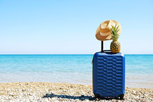 Blue Hardshell Carry-on Roller Luggage Standing With Straw Hat & Pineapple On Sandy Beach. Hard Plastic Suitcase On Wheels W/ Extended Handle. Summer Vacation Concept. Copy Space Background, Close Up.