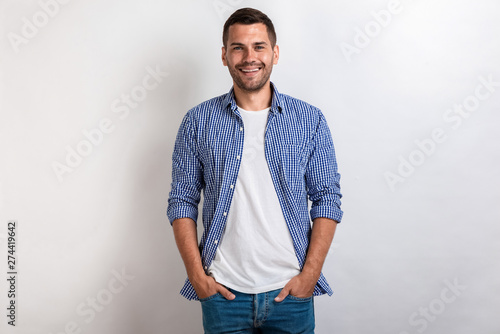 Pinturas sobre lienzo  Nice man wearing in casual clothes standing holding his arms in pocket, smiling