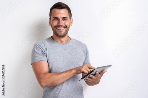 Happy man standing with ipad looking at the camera- Image Canvas-taulu