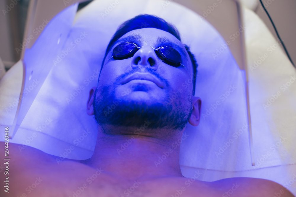 Fototapety, obrazy: Face of a calm young man lying in tanning bed in solarium