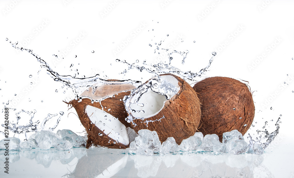 Fototapeta tropical coconut with ice and splashing water on white background