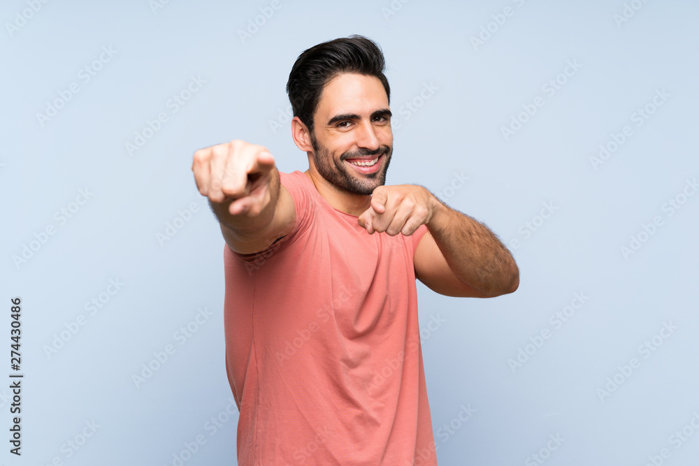 Fototapeta Handsome young man in pink shirt over isolated blue background points finger at you while smiling