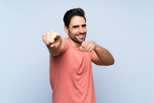 Handsome Young Man In Pink Shirt Over Isolated Blue Background Points Finger At You While Smiling