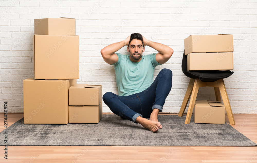 Fototapety, obrazy: Handsome young man moving in new home among boxes with surprise facial expression