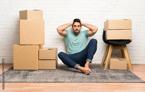 Fotografía  Handsome young man moving in new home among boxes with surprise facial expressio