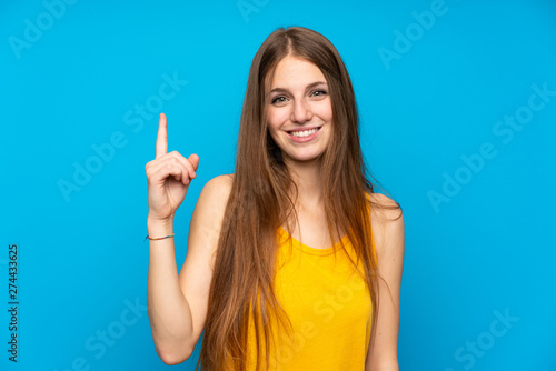 Young woman with long hair over isolated blue wall showing and lifting a finger in sign of the best