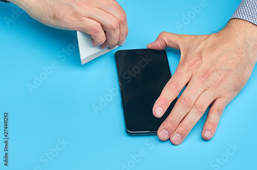 The man replacing the broken tempered glass screen protector for smartphone Fototapete